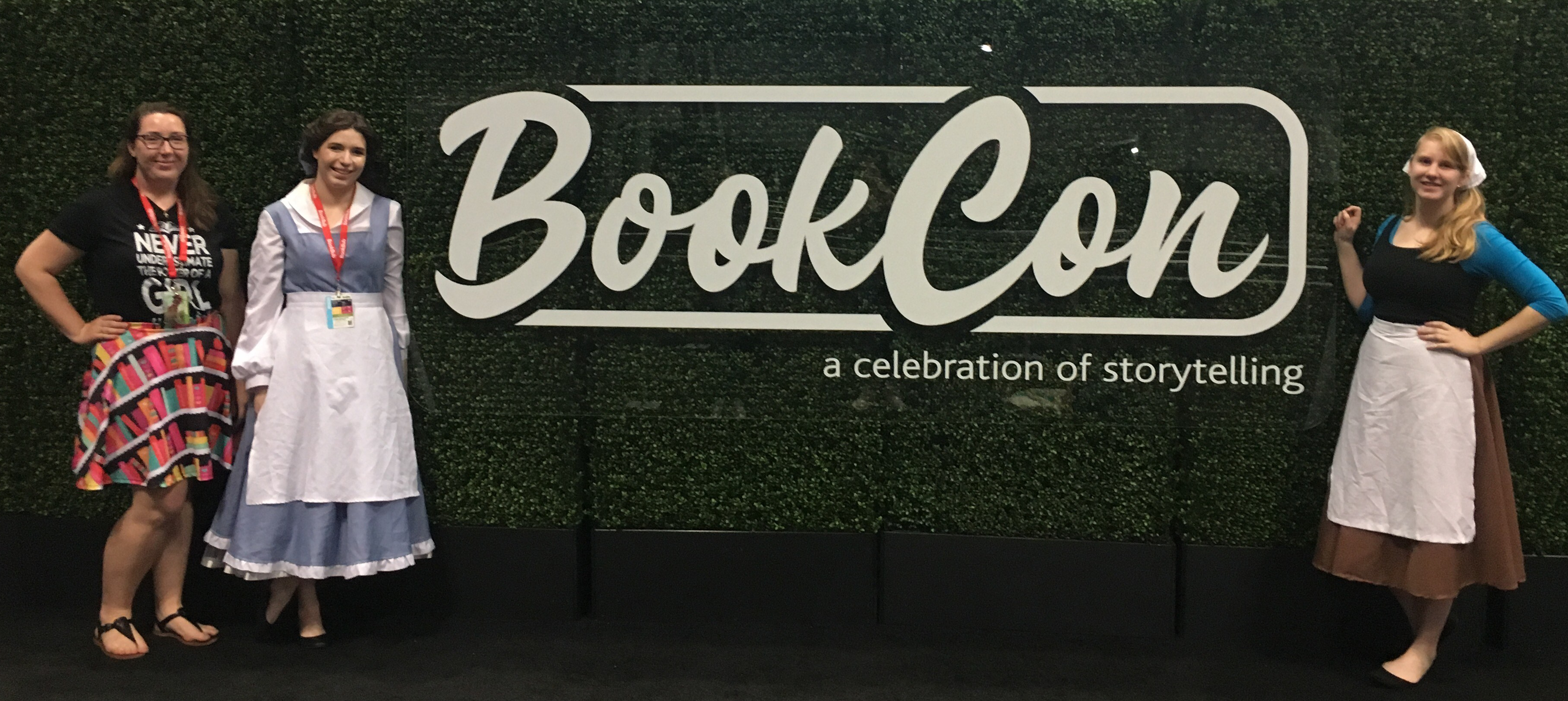 Belle and Cinderella cosplays posing in front of the BookCon sign